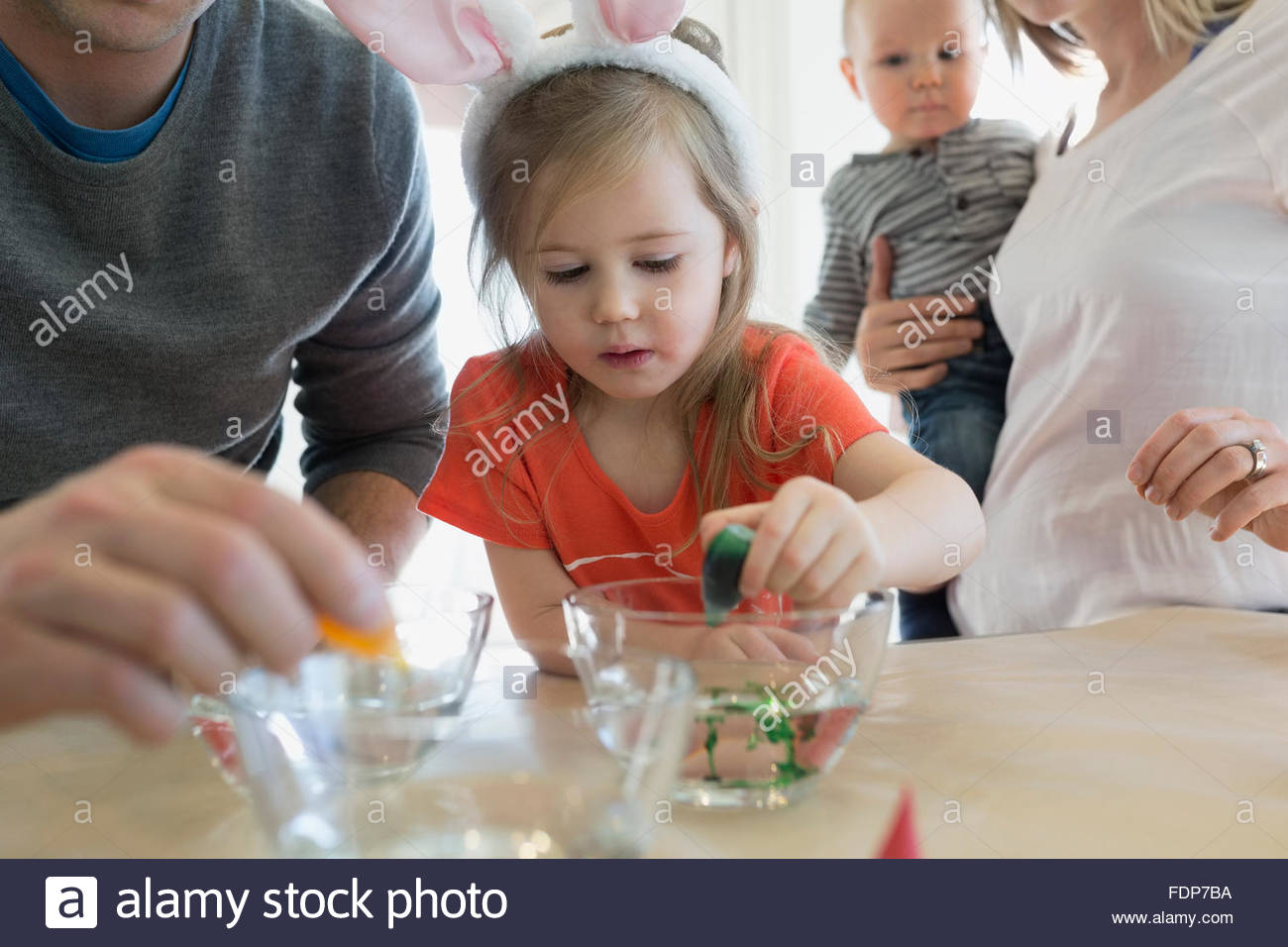 Family preparing food coloring for Easter eggs - Stock Image