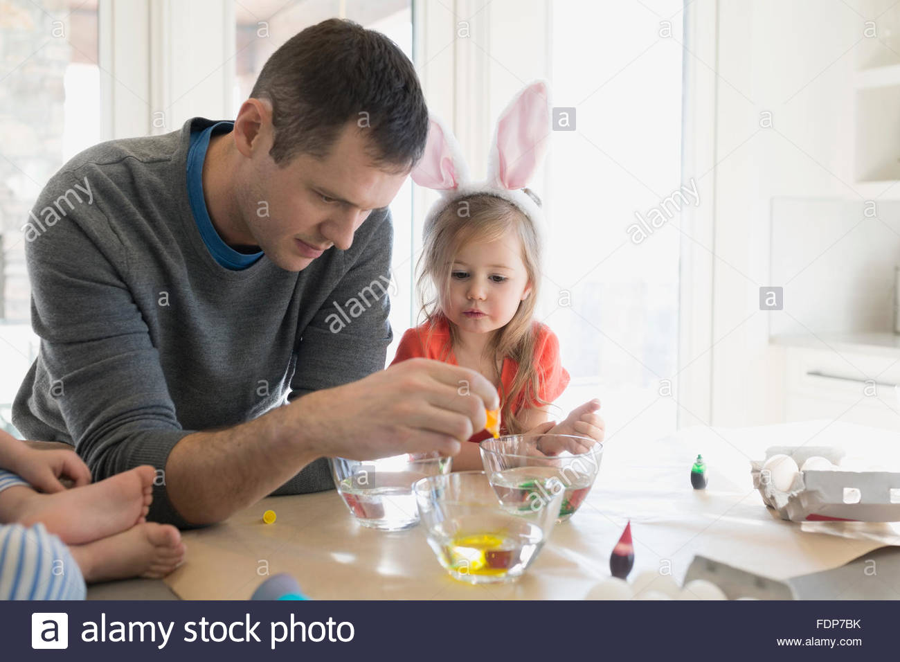 Father and daughter preparing food coloring Easter eggs - Stock Image