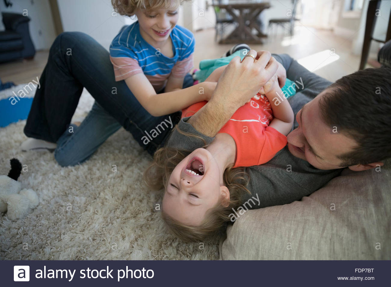Father and brother tickling sister on rug - Stock Image