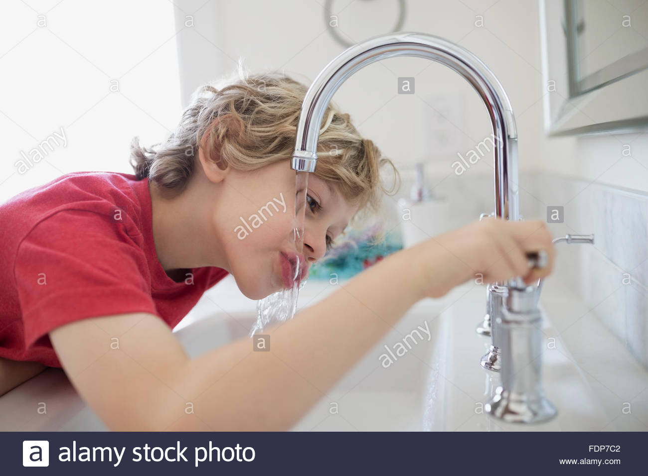 Boy drinking water from bathroom faucet - Stock Image