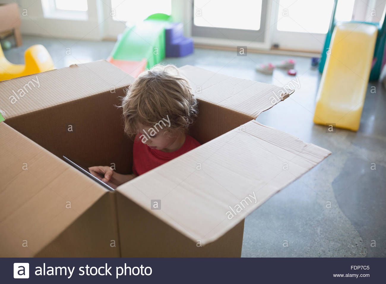 Boy using digital tablet inside cardboard box - Stock Image