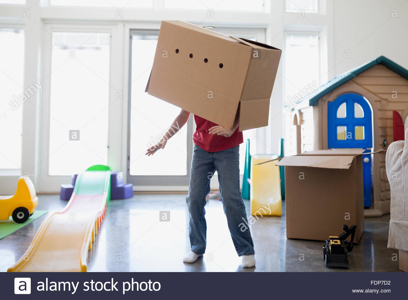 Playful boy dancing with cardboard box on head - Stock Image