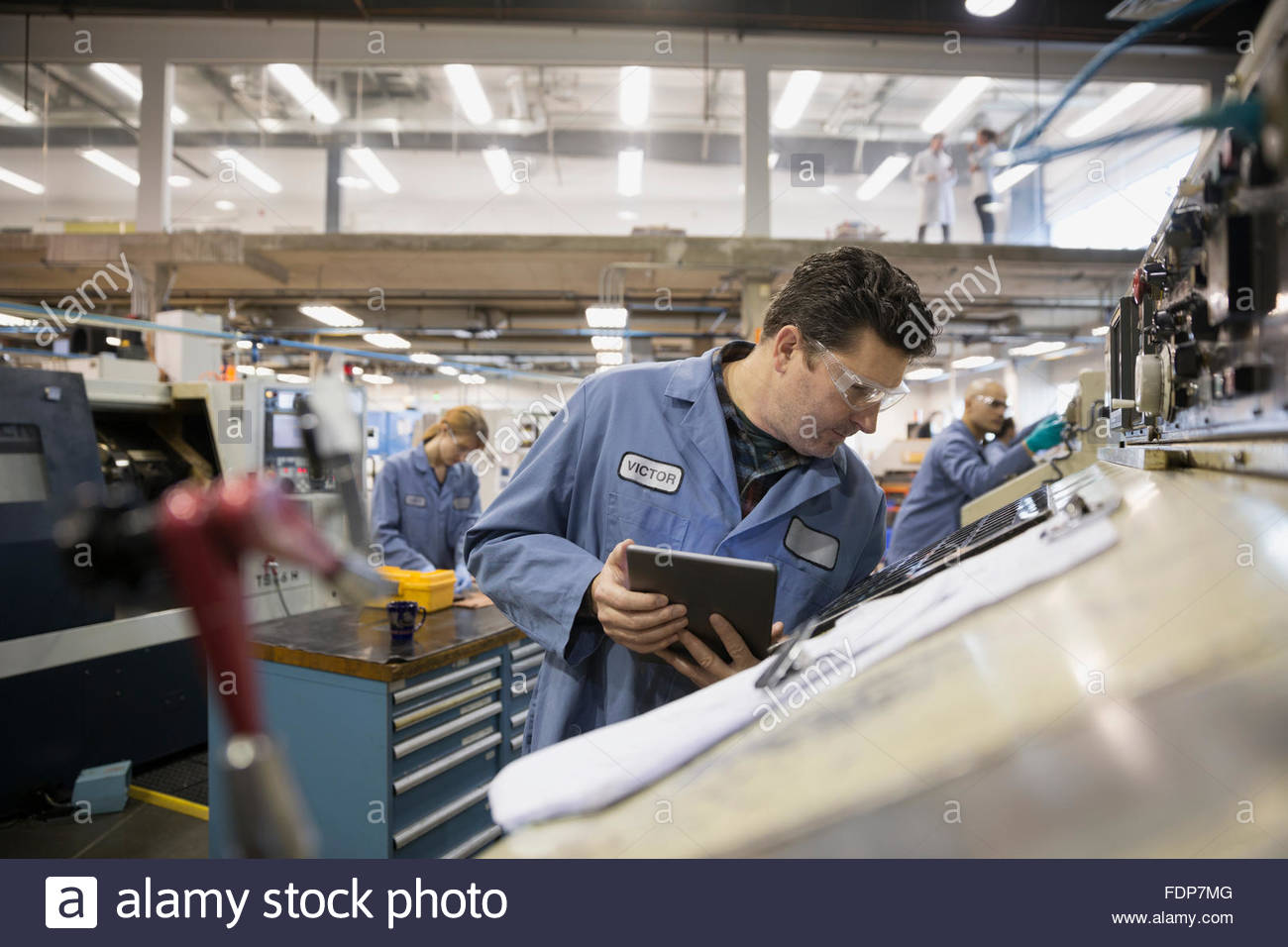 Worker with digital tablet examining machinery in factory - Stock Image