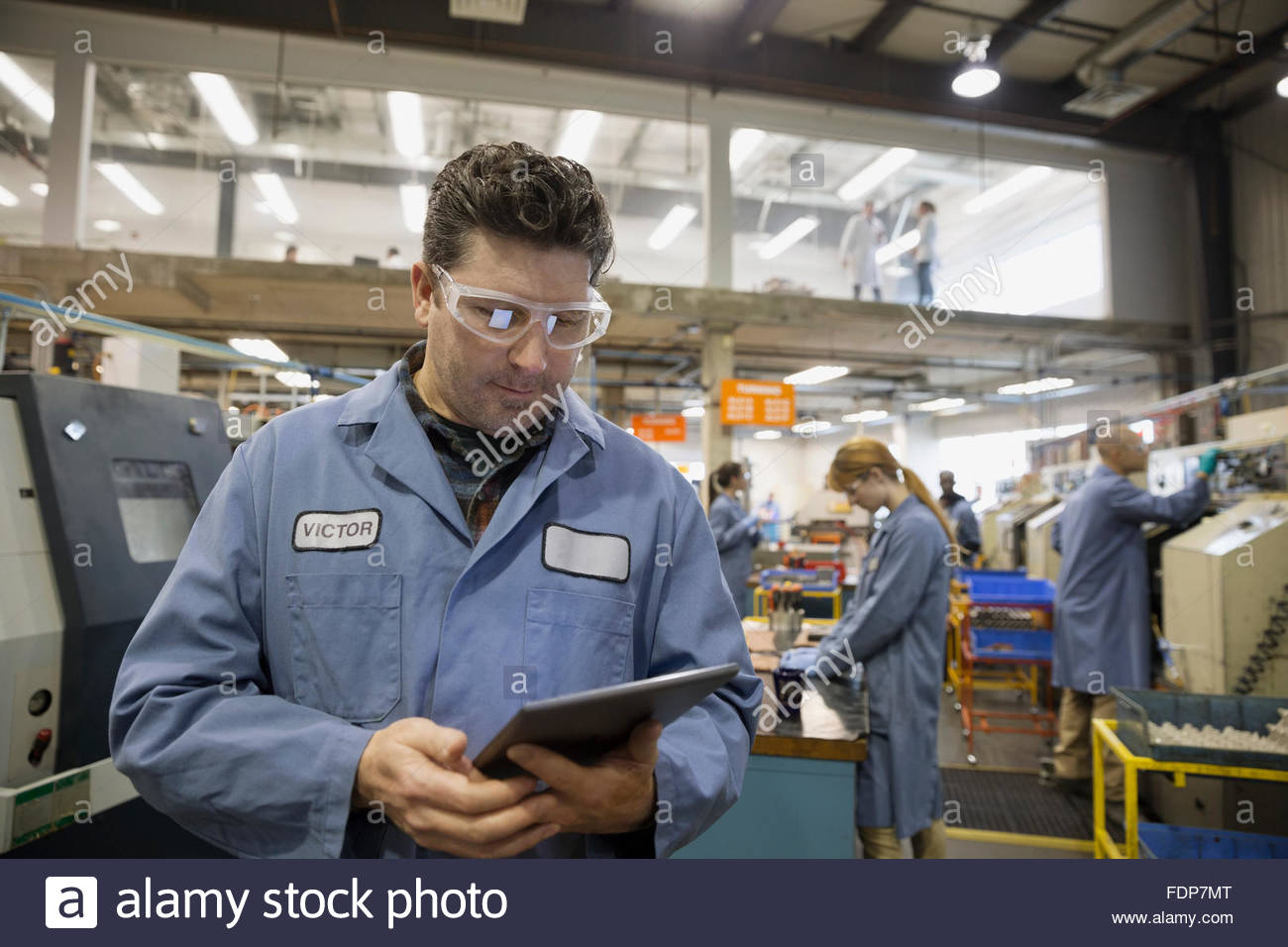 Worker with digital tablet in textile factory - Stock Image