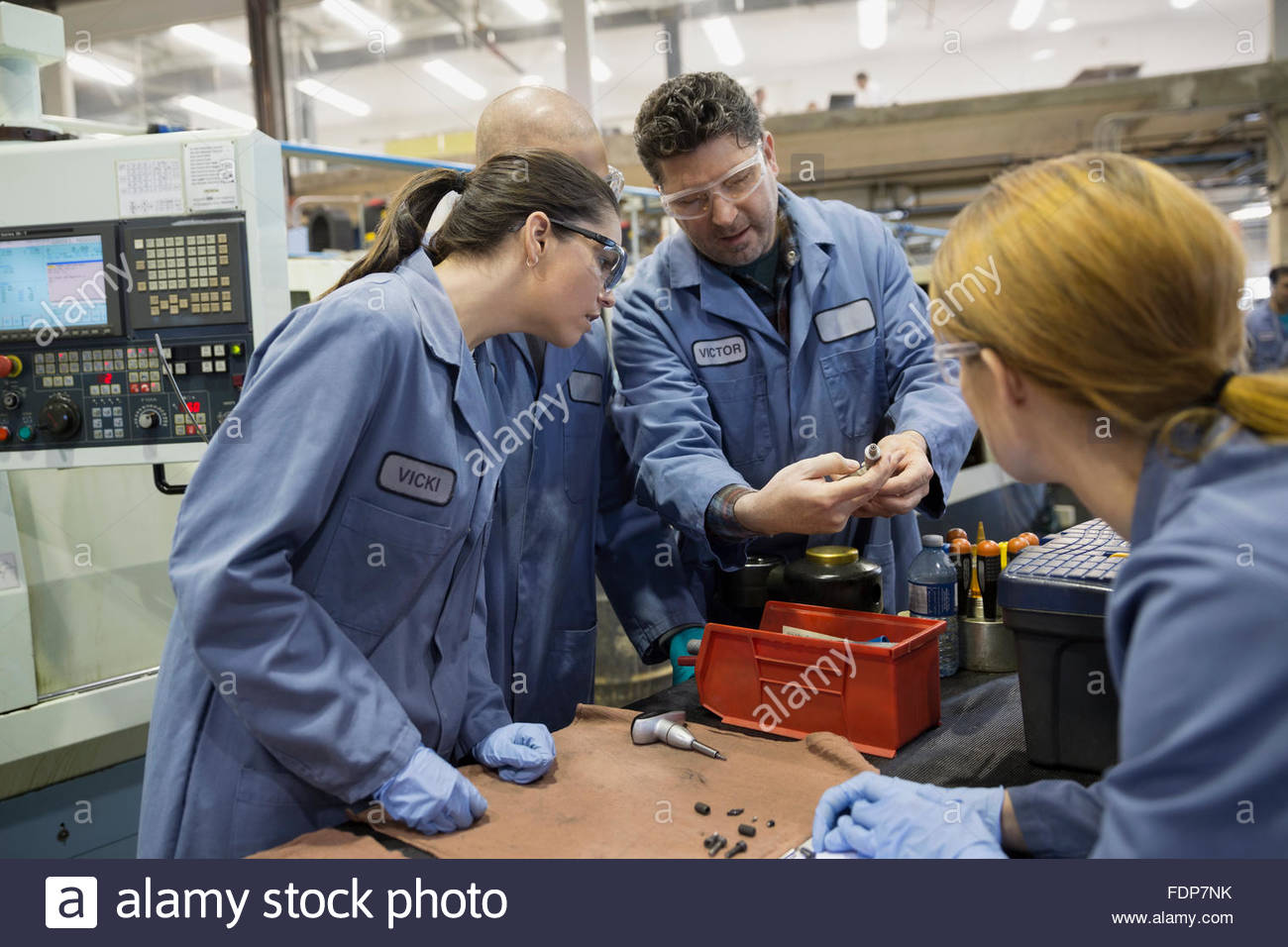 Workers examining parts in factory - Stock Image