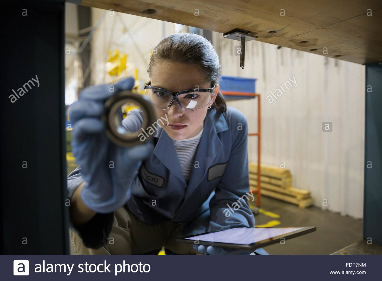 Focused worker with digital tablet examining part factory - Stock Image