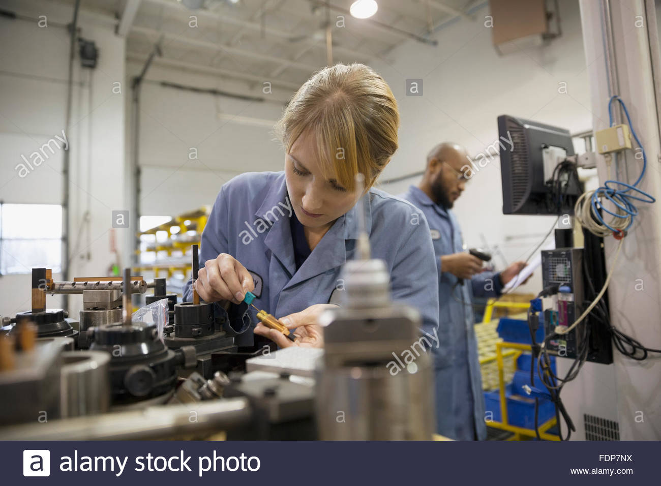 Worker examining part in factory - Stock Image