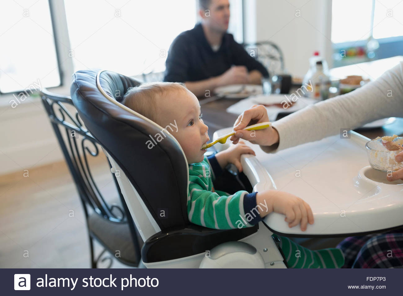 Mother feeding baby boy in high chair - Stock Image