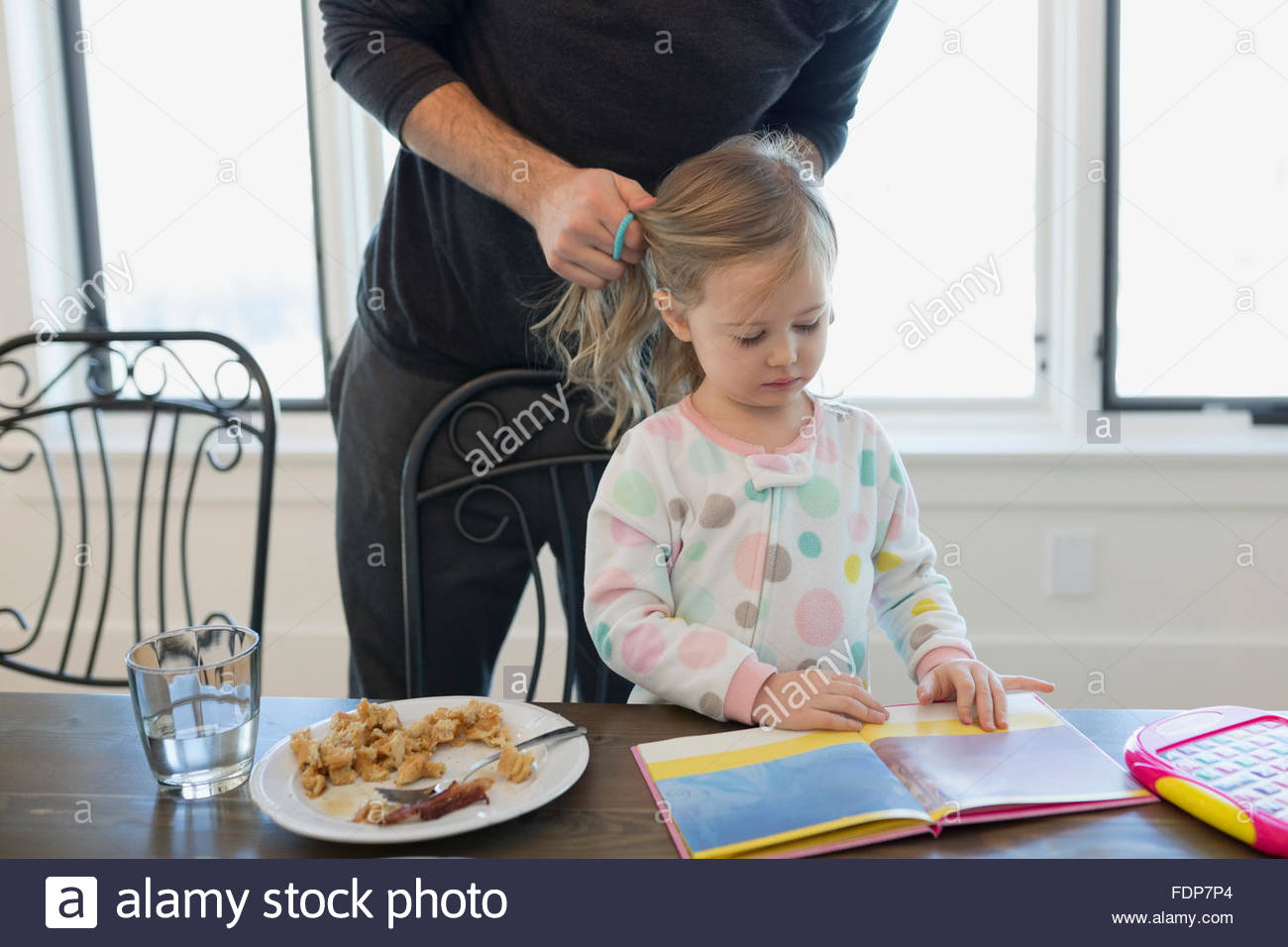 father fixing daughters hair reading - Stock Image