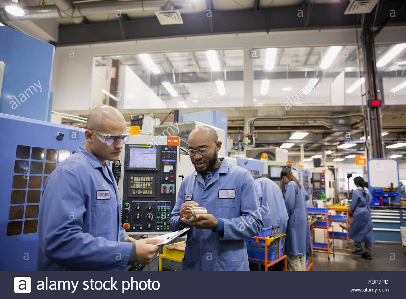 Workers discussing part in textile factory - Stock Image