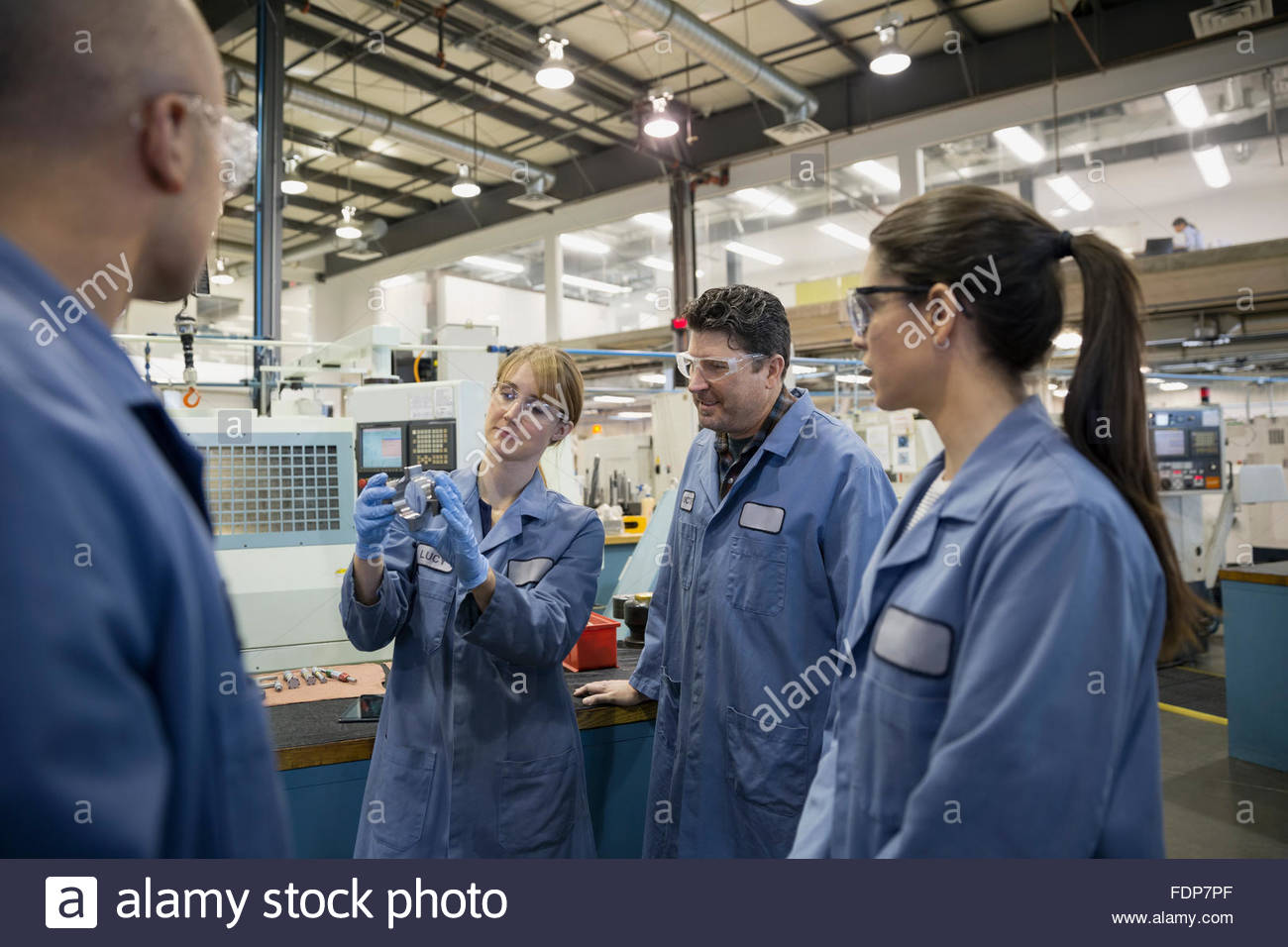 Workers discussing part in factory - Stock Image