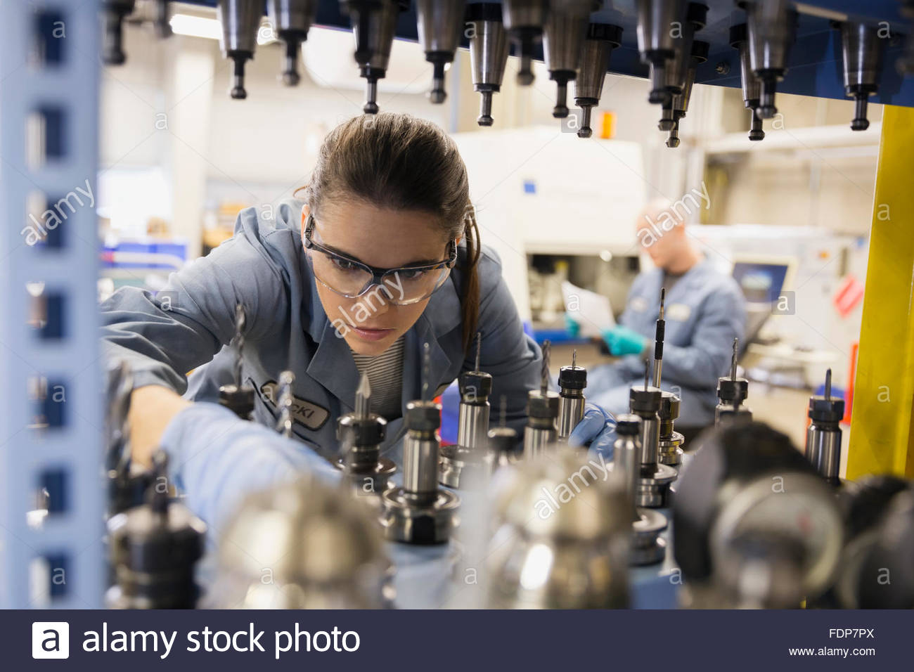 Worker examining machinery in textile factory - Stock Image