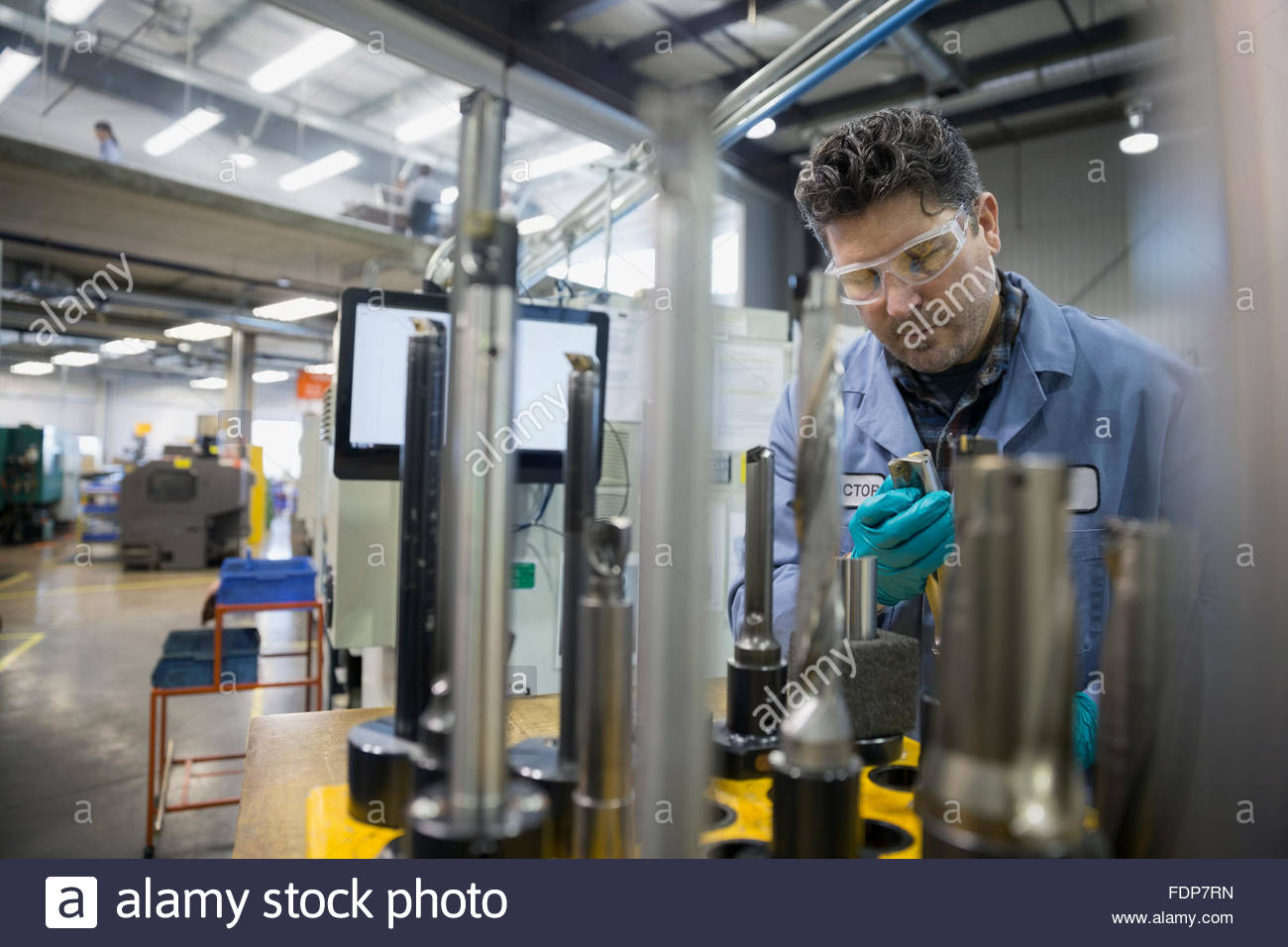 Worker examining machine part in factory - Stock Image