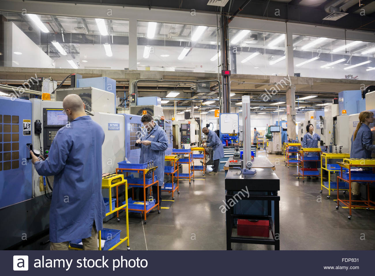 Workers at machinery in textile factory - Stock Image