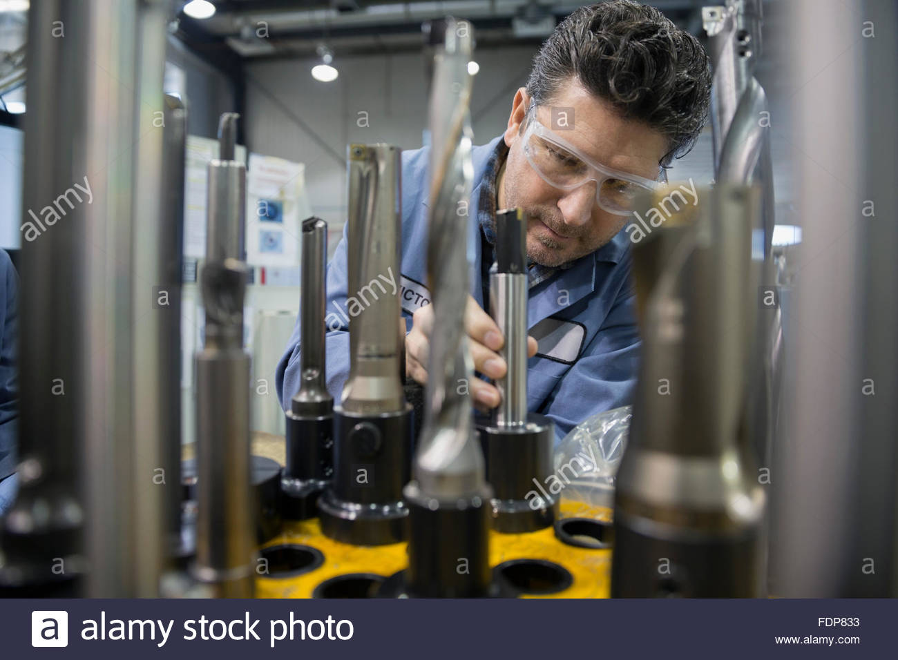 Worker examining machinery in factory - Stock Image