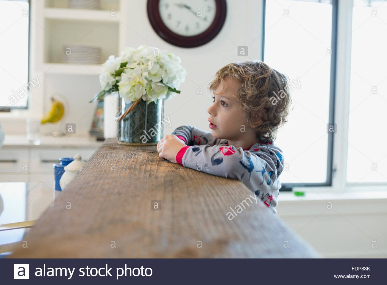 Boy in pajamas leaning on kitchen breakfast bar - Stock Image