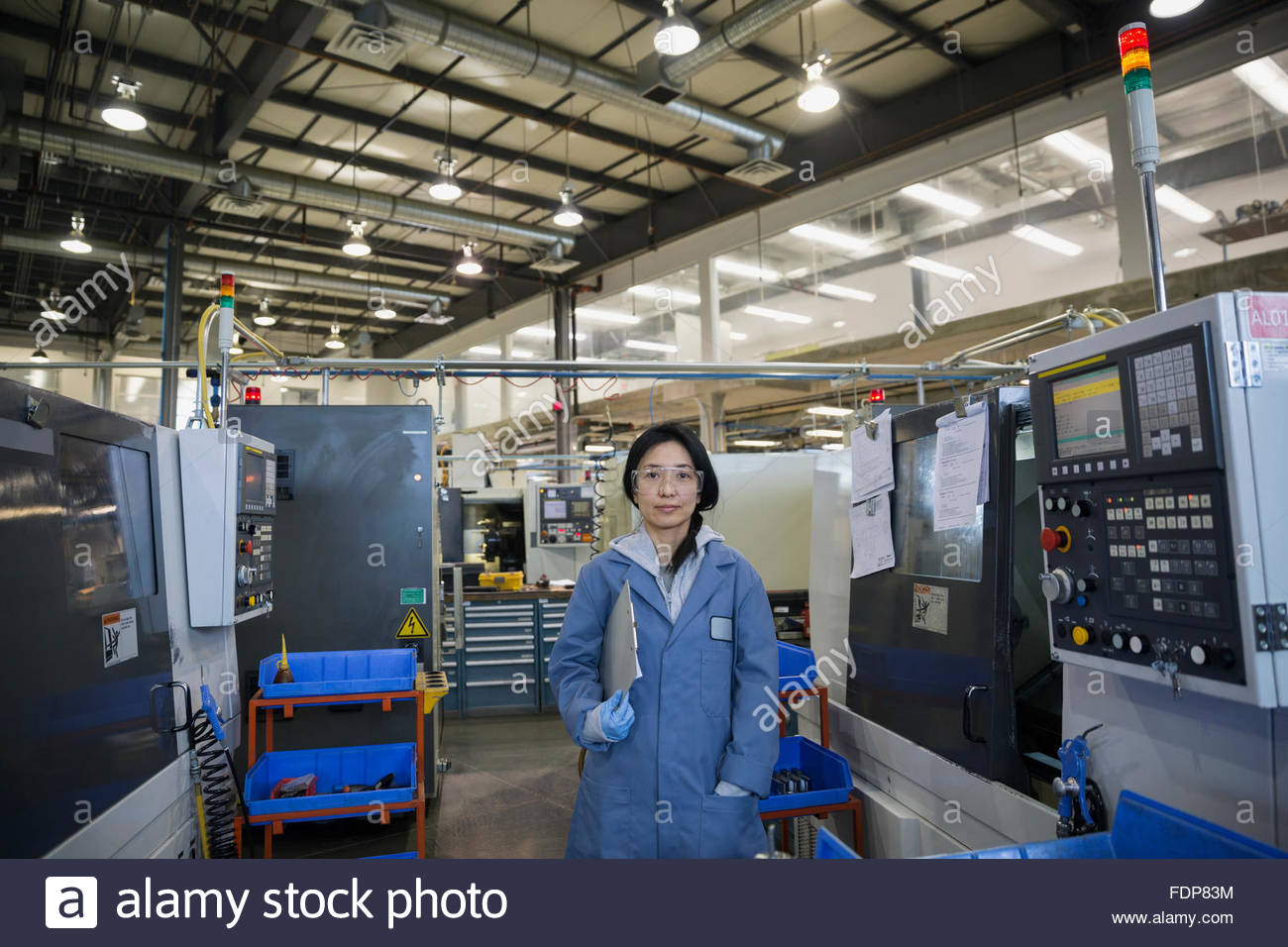 Portrait confident worker with clipboard in textile factory - Stock Image
