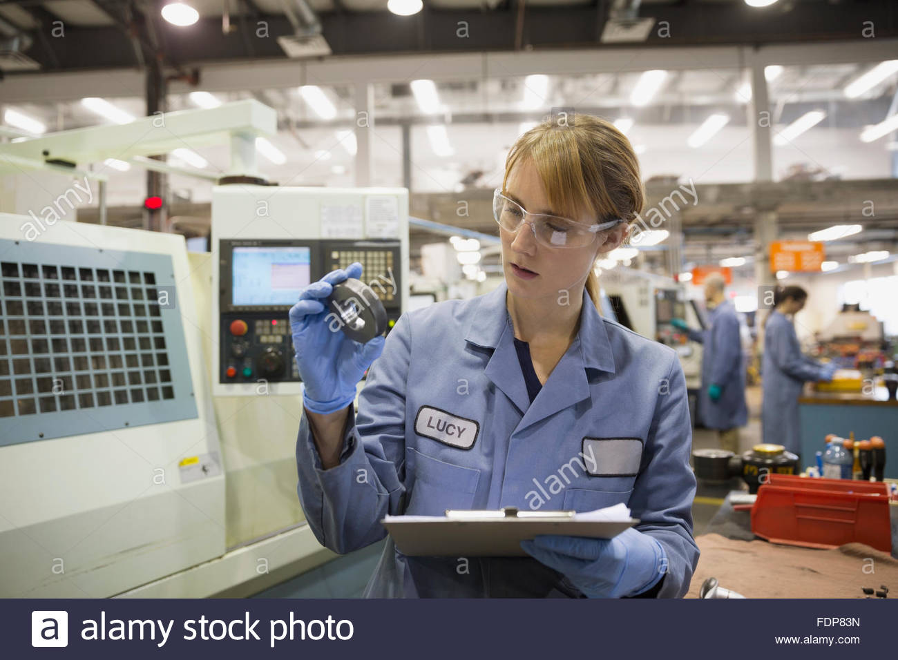 Worker with clipboard examining part in factory - Stock Image