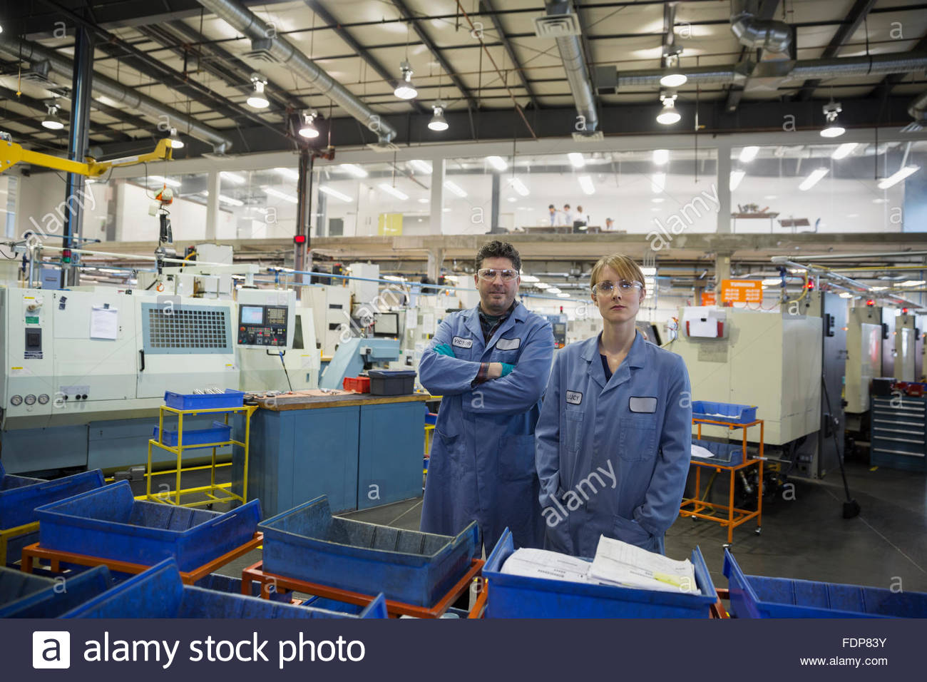 Portrait confident workers in textile factory - Stock Image