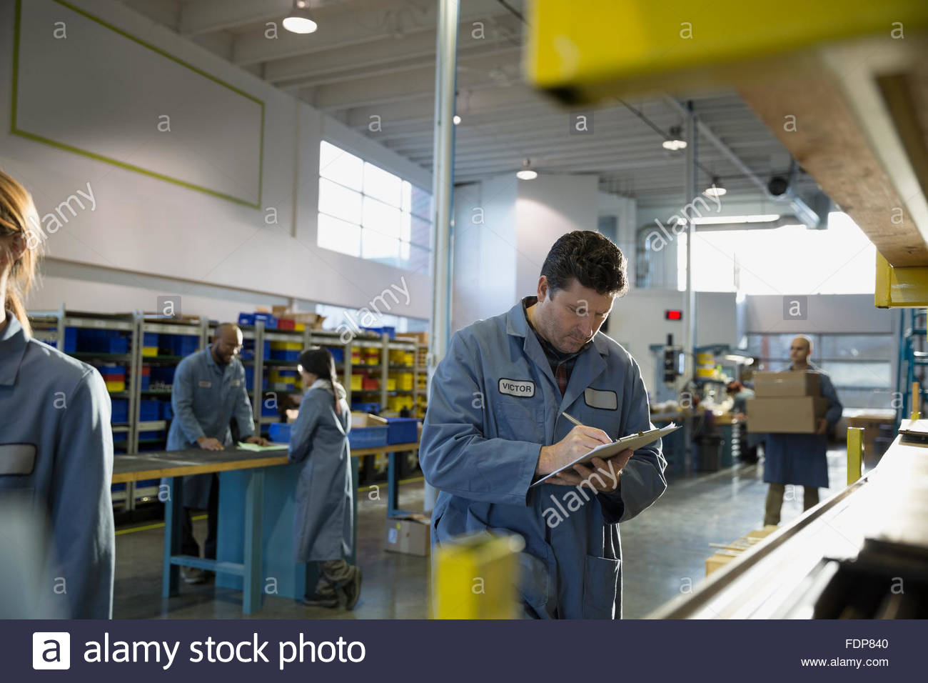 Worker with clipboard in textile factory - Stock Image
