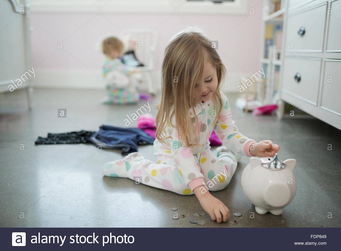Girl placing coins in piggy bank bedroom floor - Stock Image