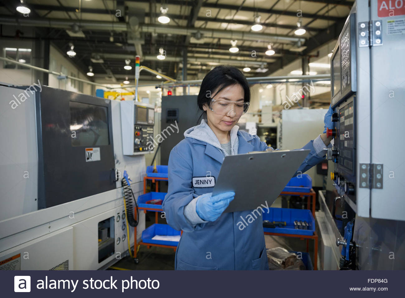 Worker looking down at clipboard in textile factory - Stock Image