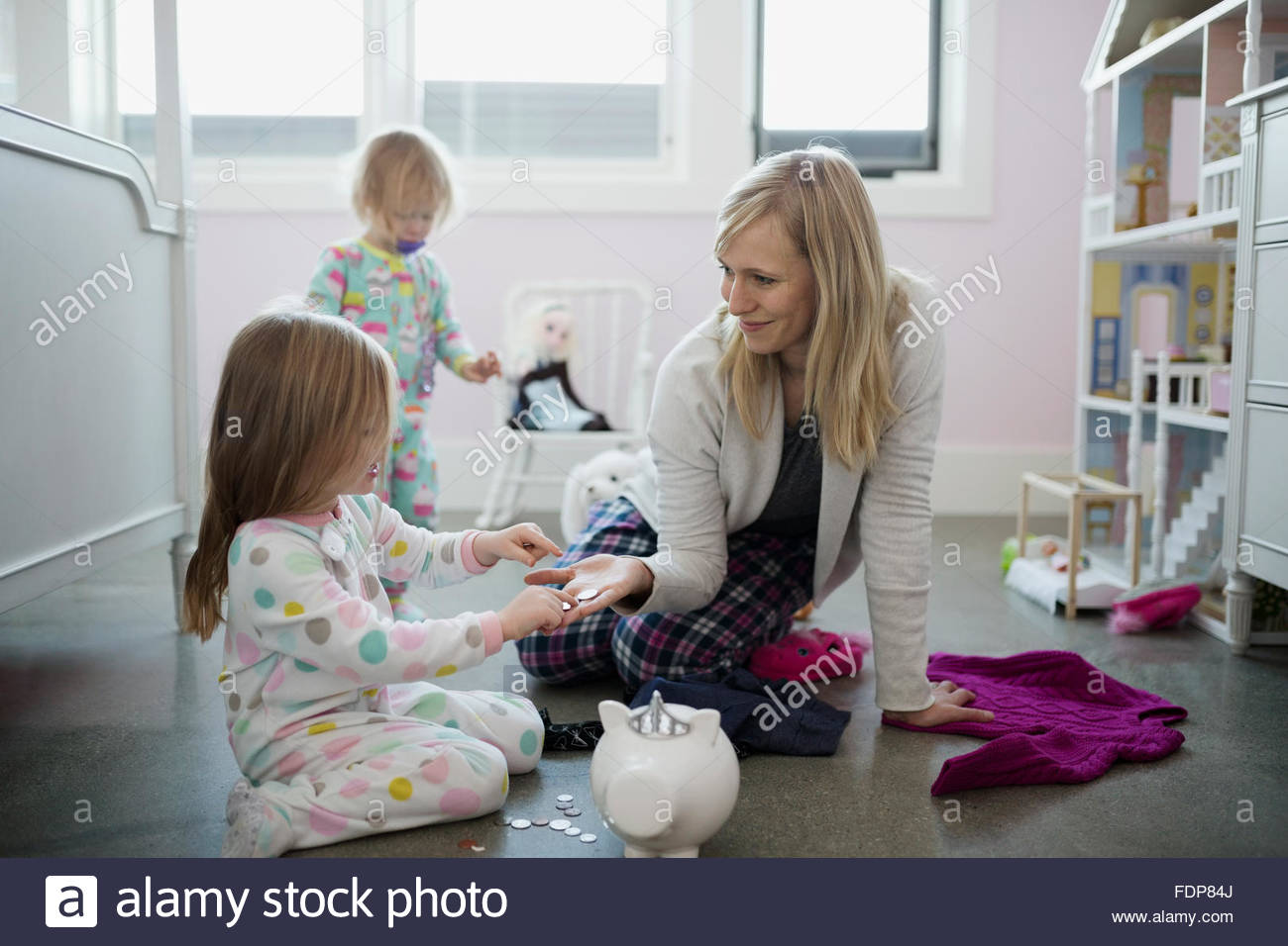 Mother and daughter placing coins in piggy bank - Stock Image