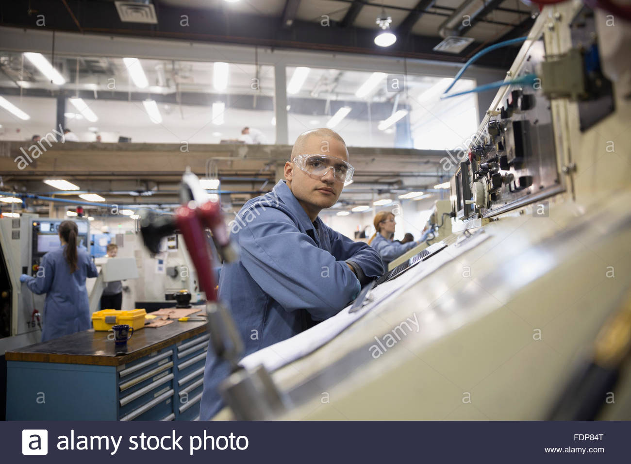 Portrait serious worker in textile factory - Stock Image