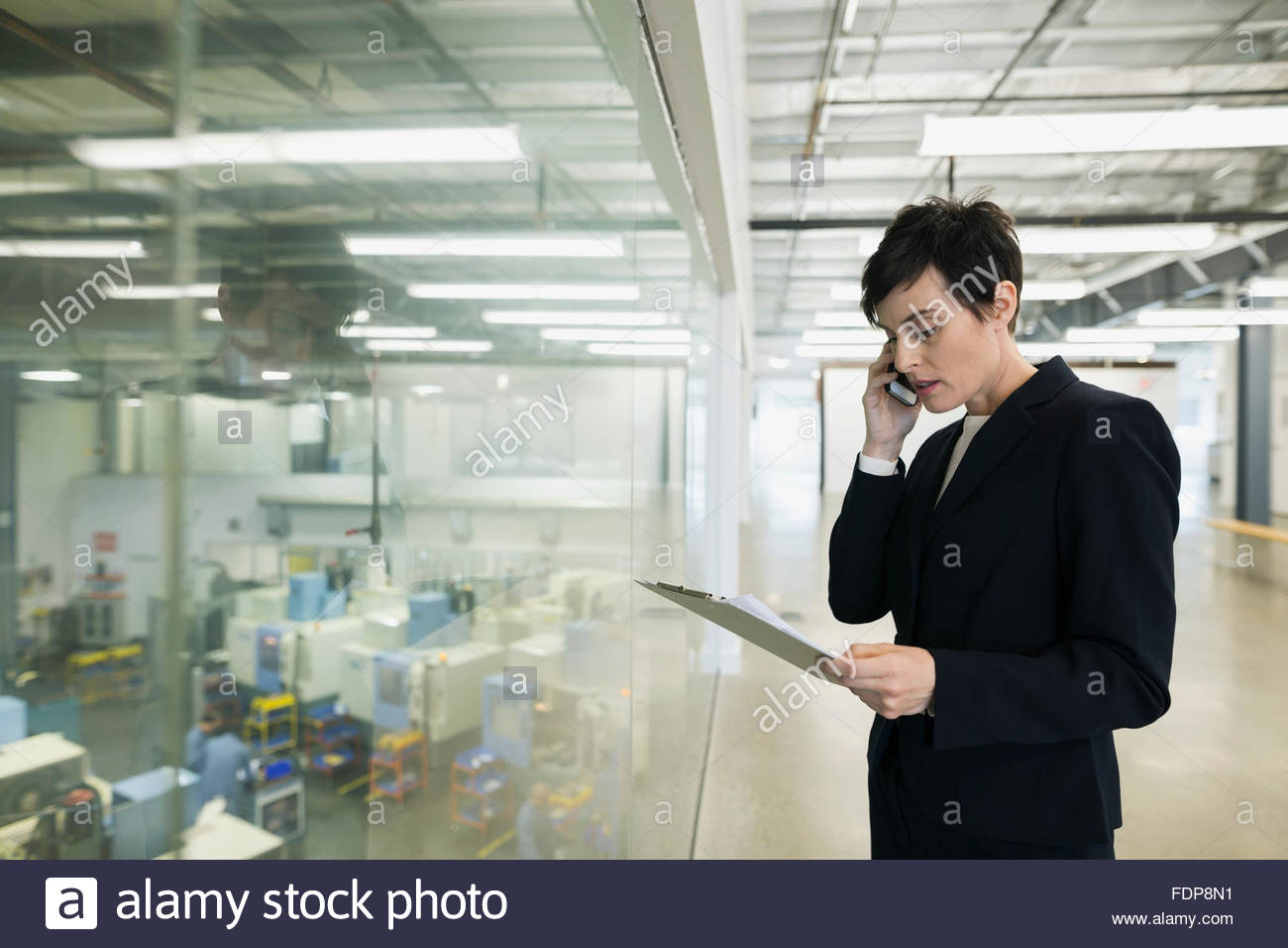 Manager with clipboard talking on cell phone factory - Stock Image