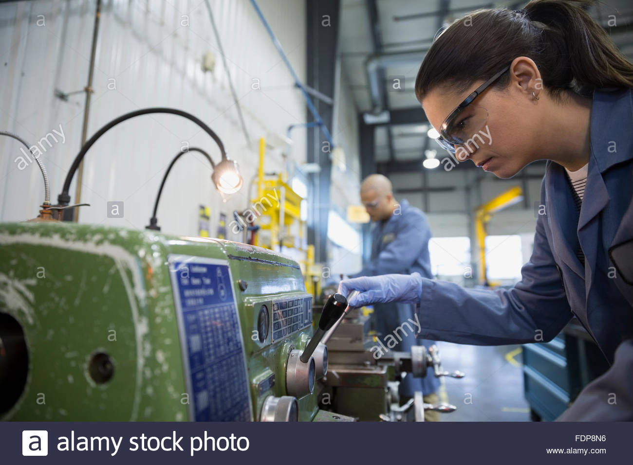 Worker using machinery in textile factory - Stock Image
