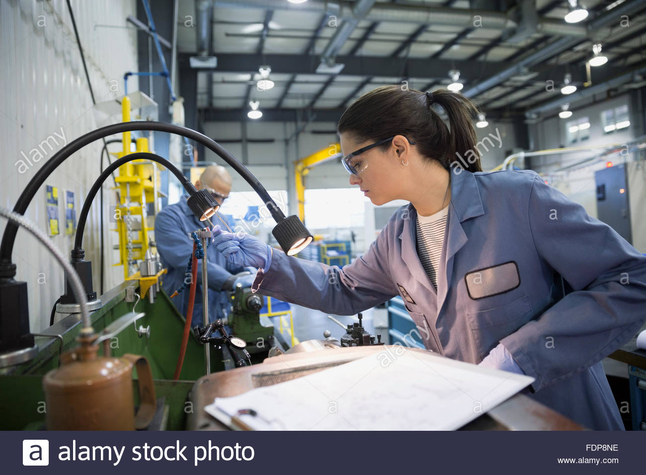 Engineer with clipboard at machinery in textile factory - Stock Image