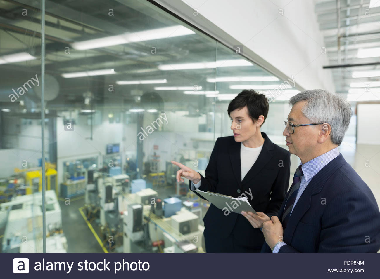 Managers with clipboard looking from window onto factory - Stock Image