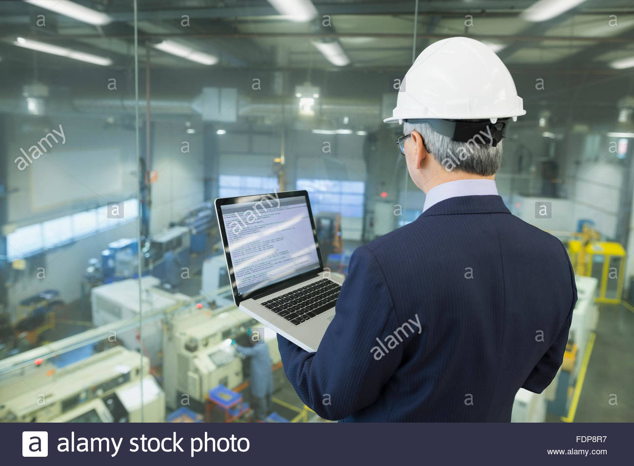 Manager with laptop looking out window onto factory - Stock Image