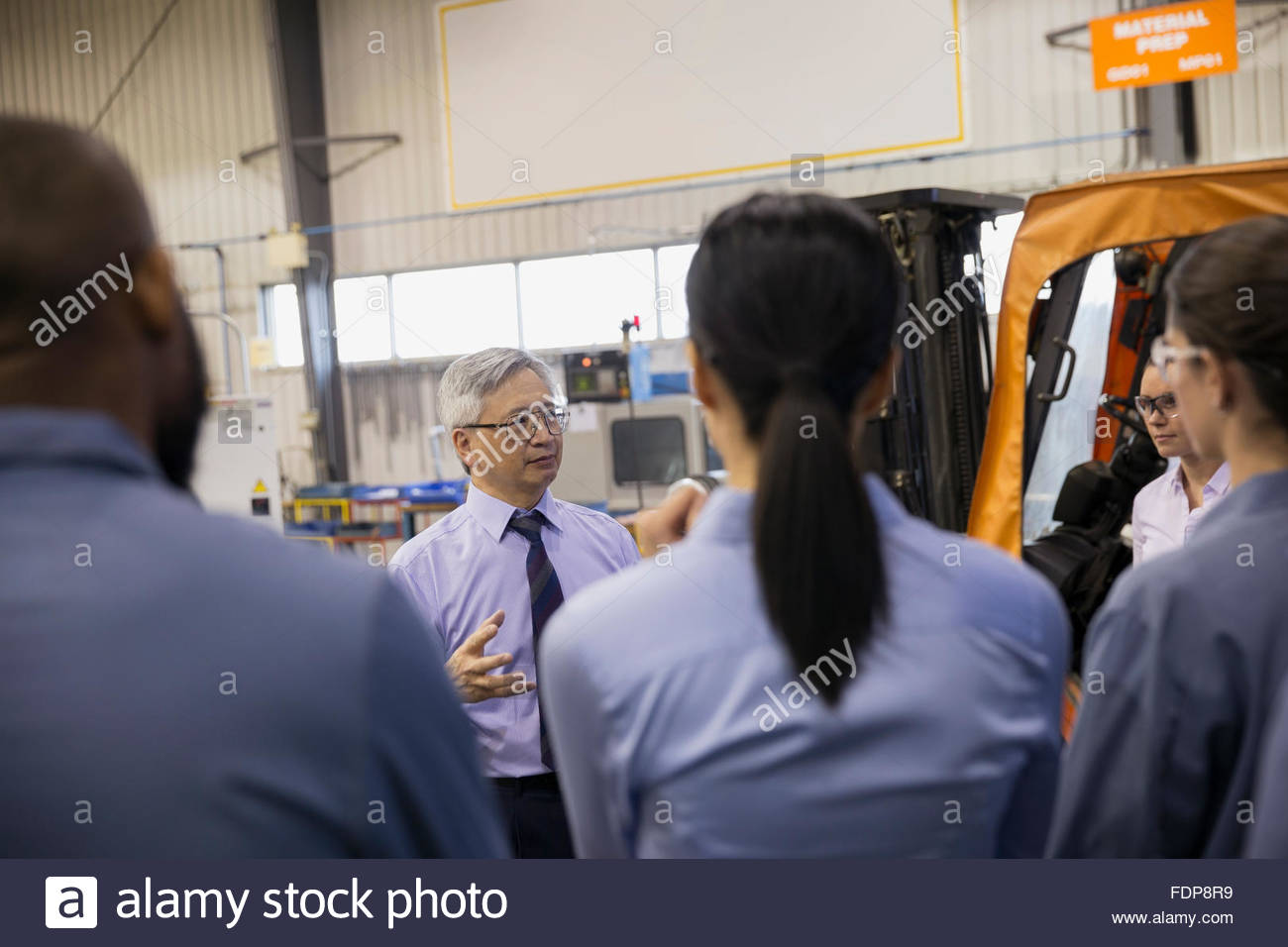 Manager leading team meeting in factory - Stock Image
