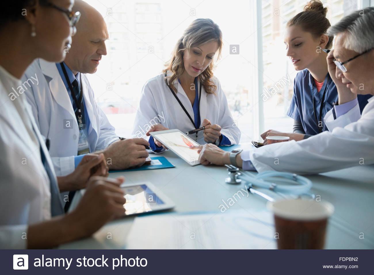 Doctors using digital tablet in meeting - Stock Image