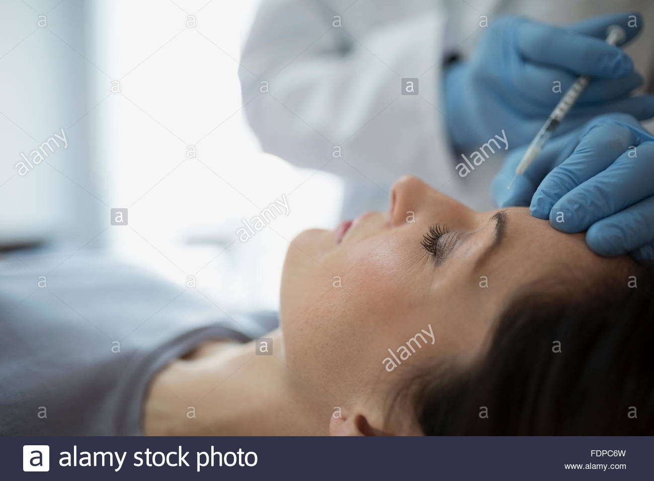 Woman receiving Botox injection in forehead - Stock Image
