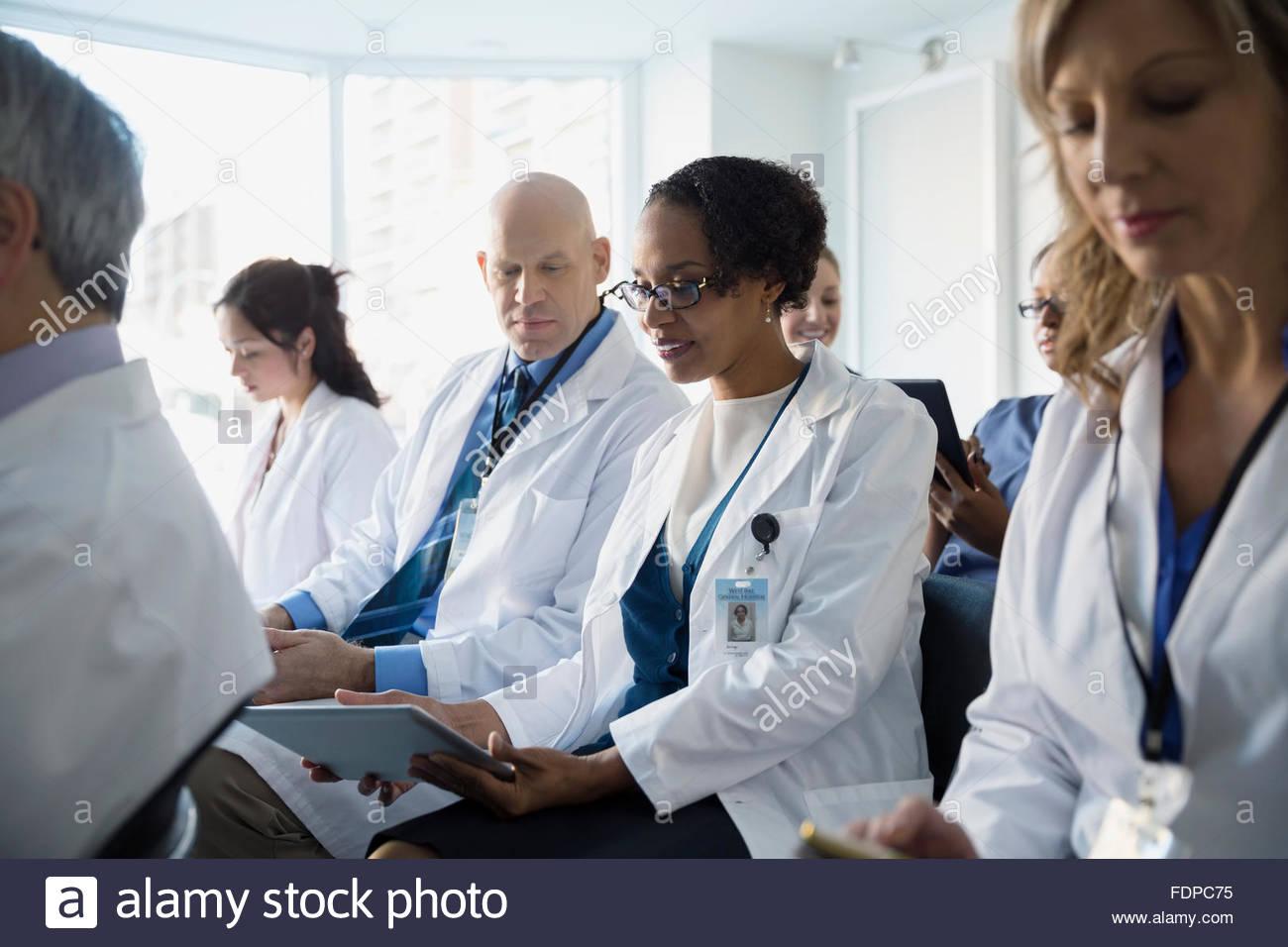 Doctors using digital tablet in seminar audience - Stock Image