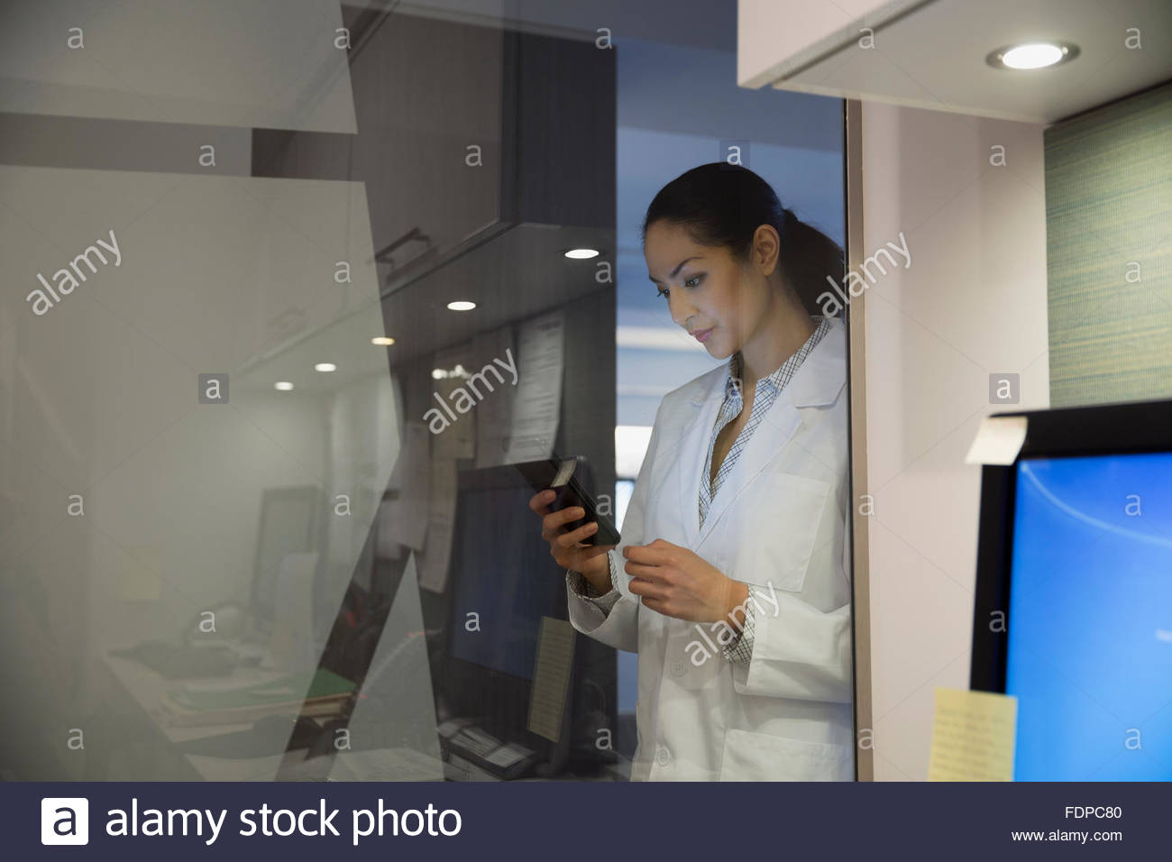 Doctor texting at glass wall in clinic Stock Photo