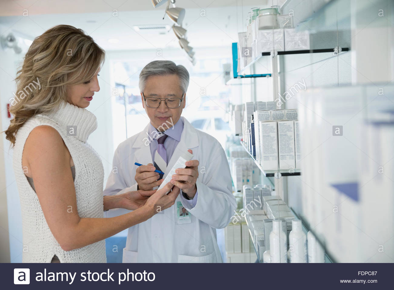 Esthetician discussing product with patient in lobby - Stock Image