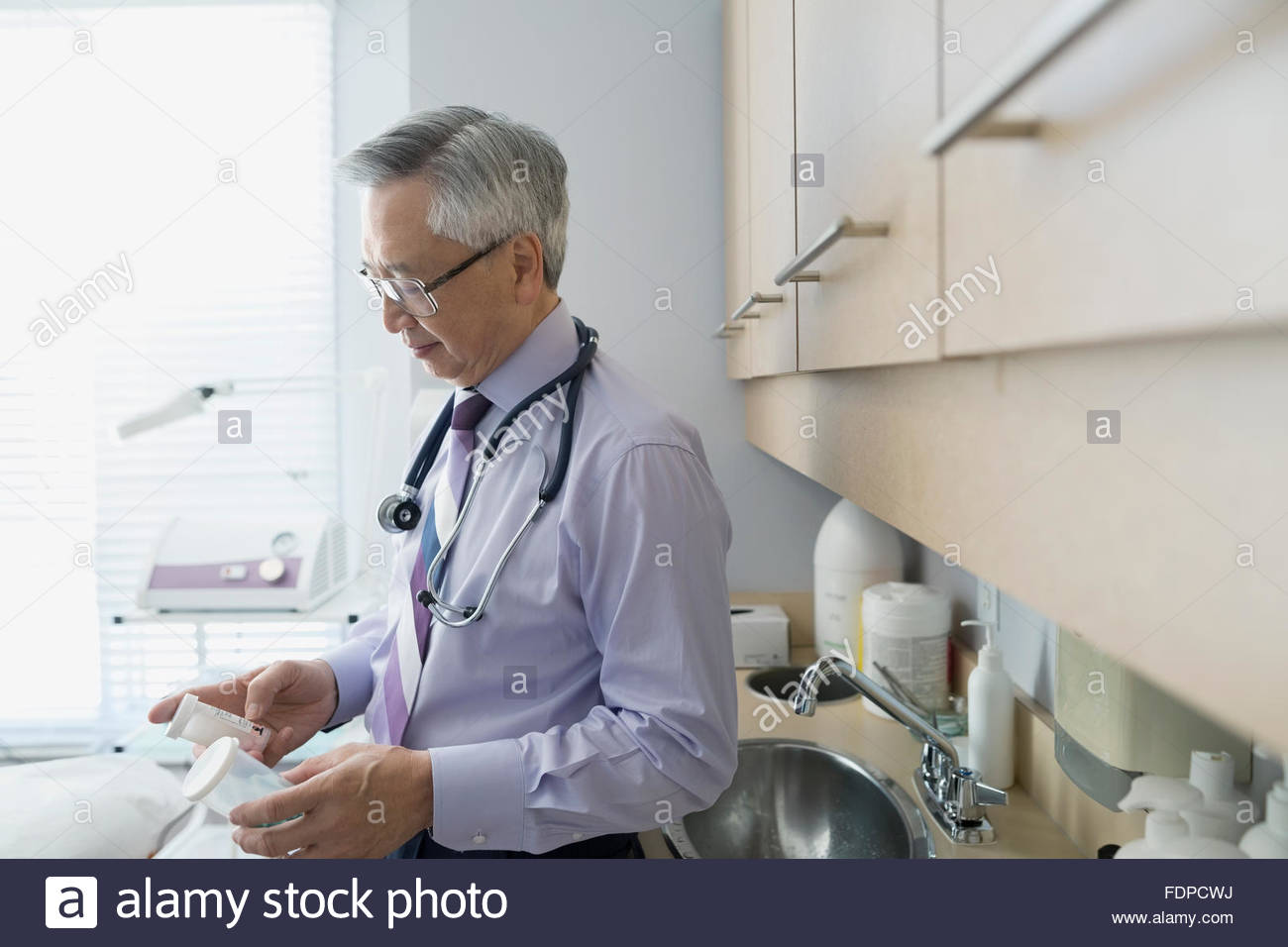 Doctor reviewing specimens in examination room - Stock Image