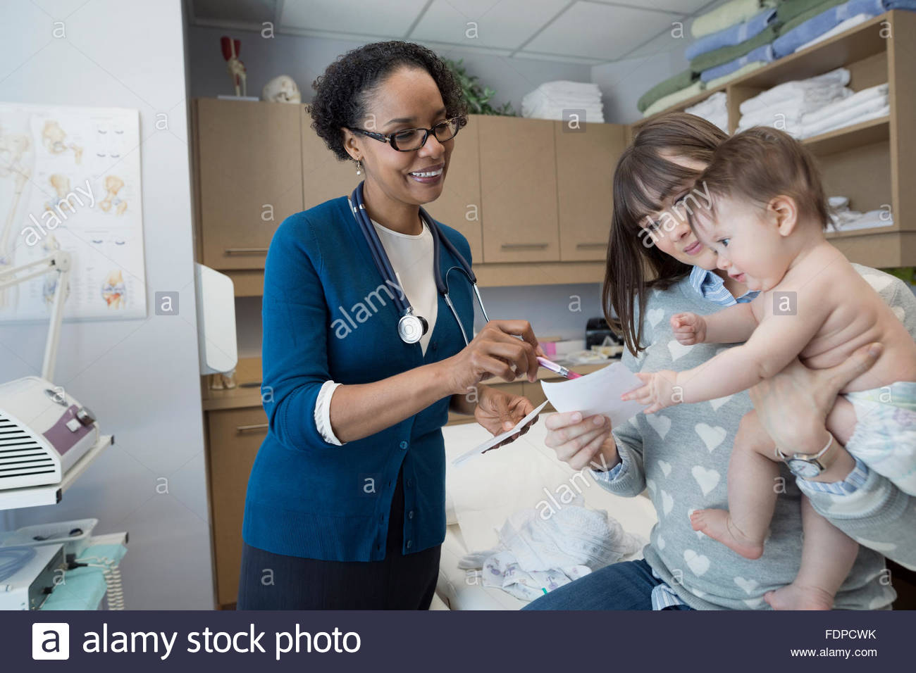 Pediatrician explaining prescription to mother and baby - Stock Image