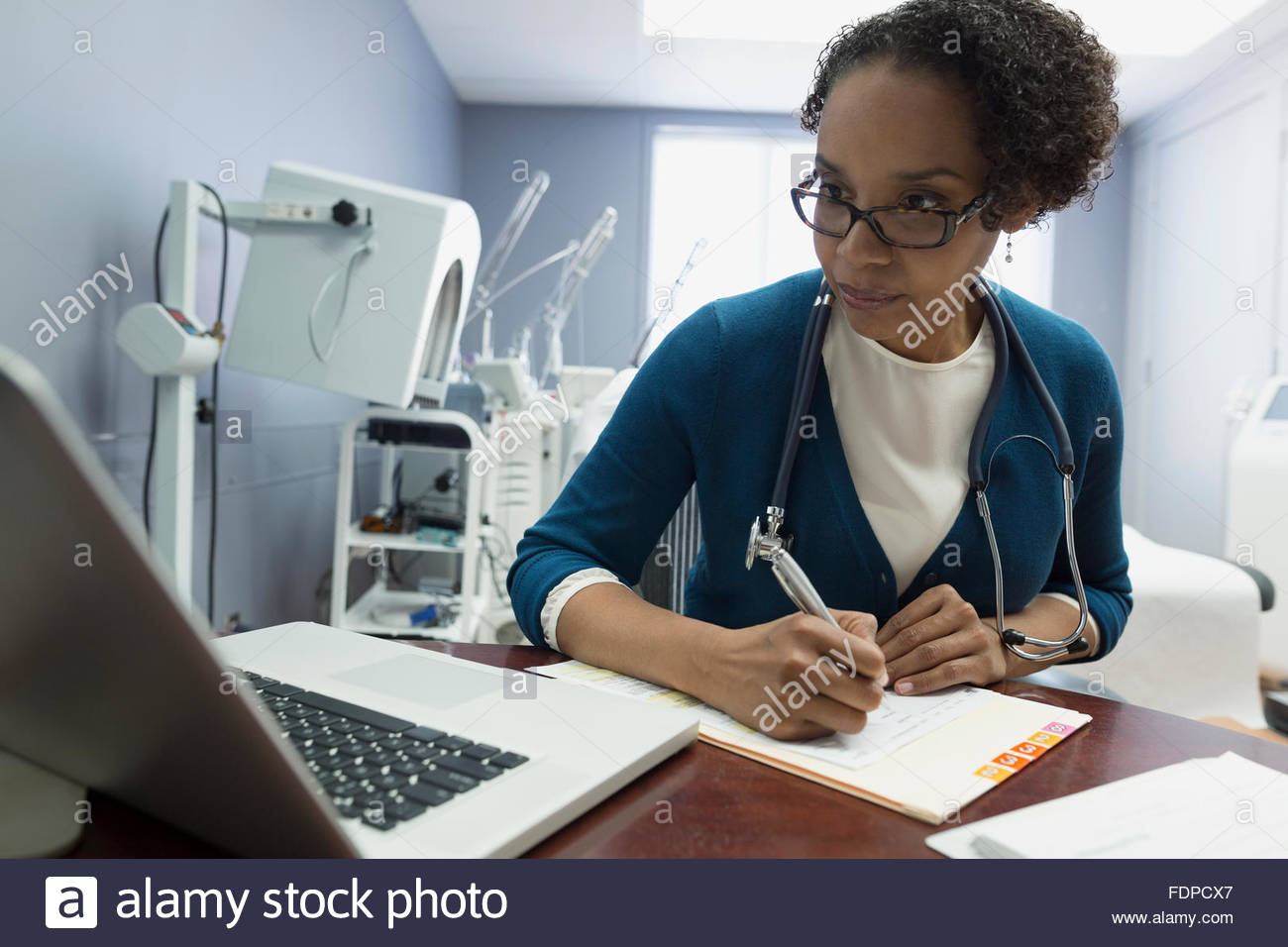 Doctor at laptop taking notes on medical record - Stock Image