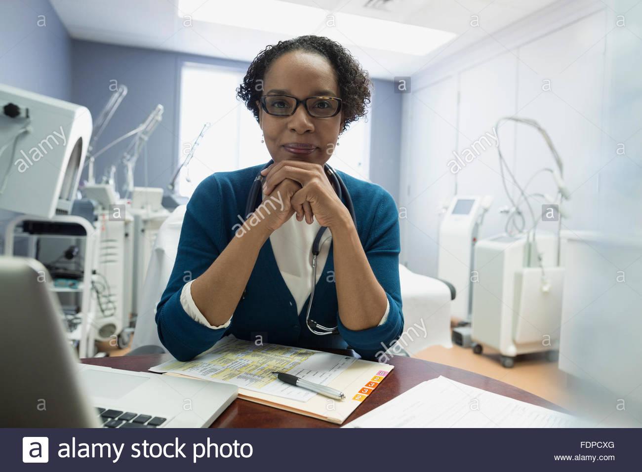 Portrait confident doctor at laptop - Stock Image
