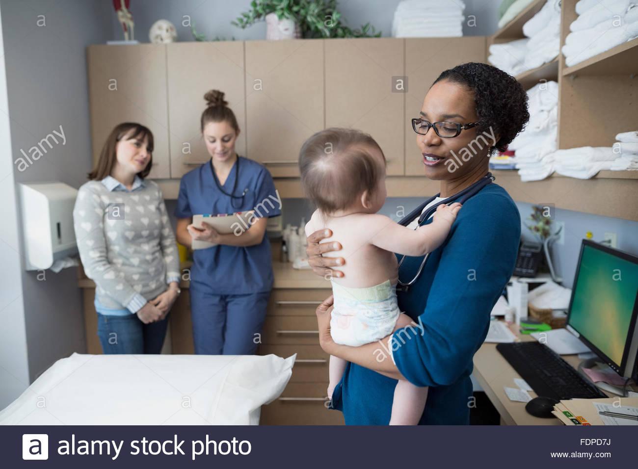 Pediatrician holding baby in examination room - Stock Image