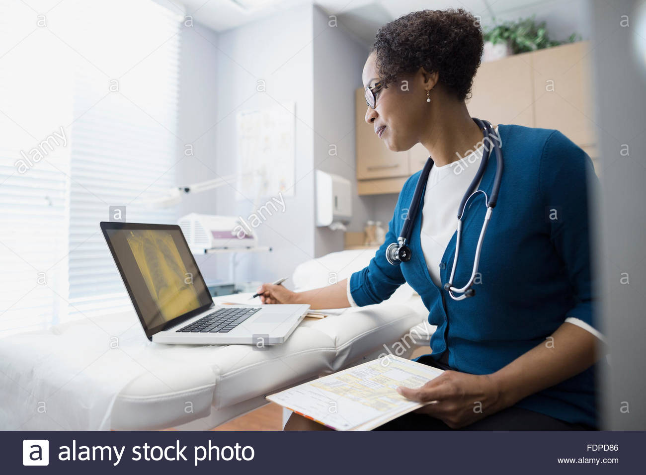 Doctor working at laptop in examination room - Stock Image
