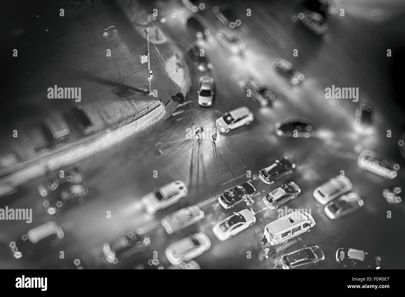 People at night walk across a pedestrian crossing in a busy city traffic jam. The miniature style effect blurs out - Stock Image