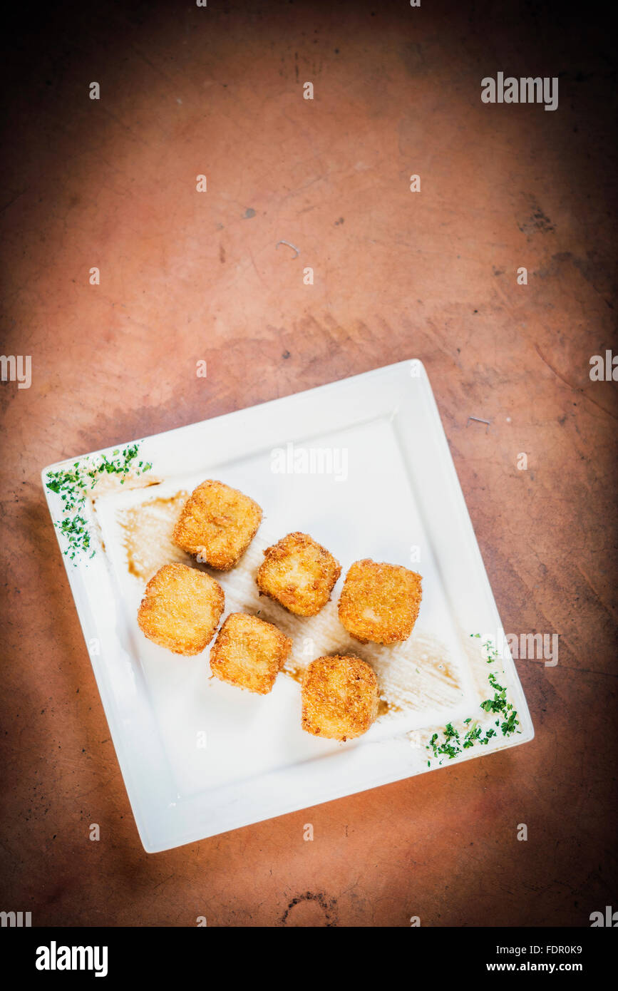 fried breaded vegeatrian potato and vegetable cubes croquettes - Stock Image