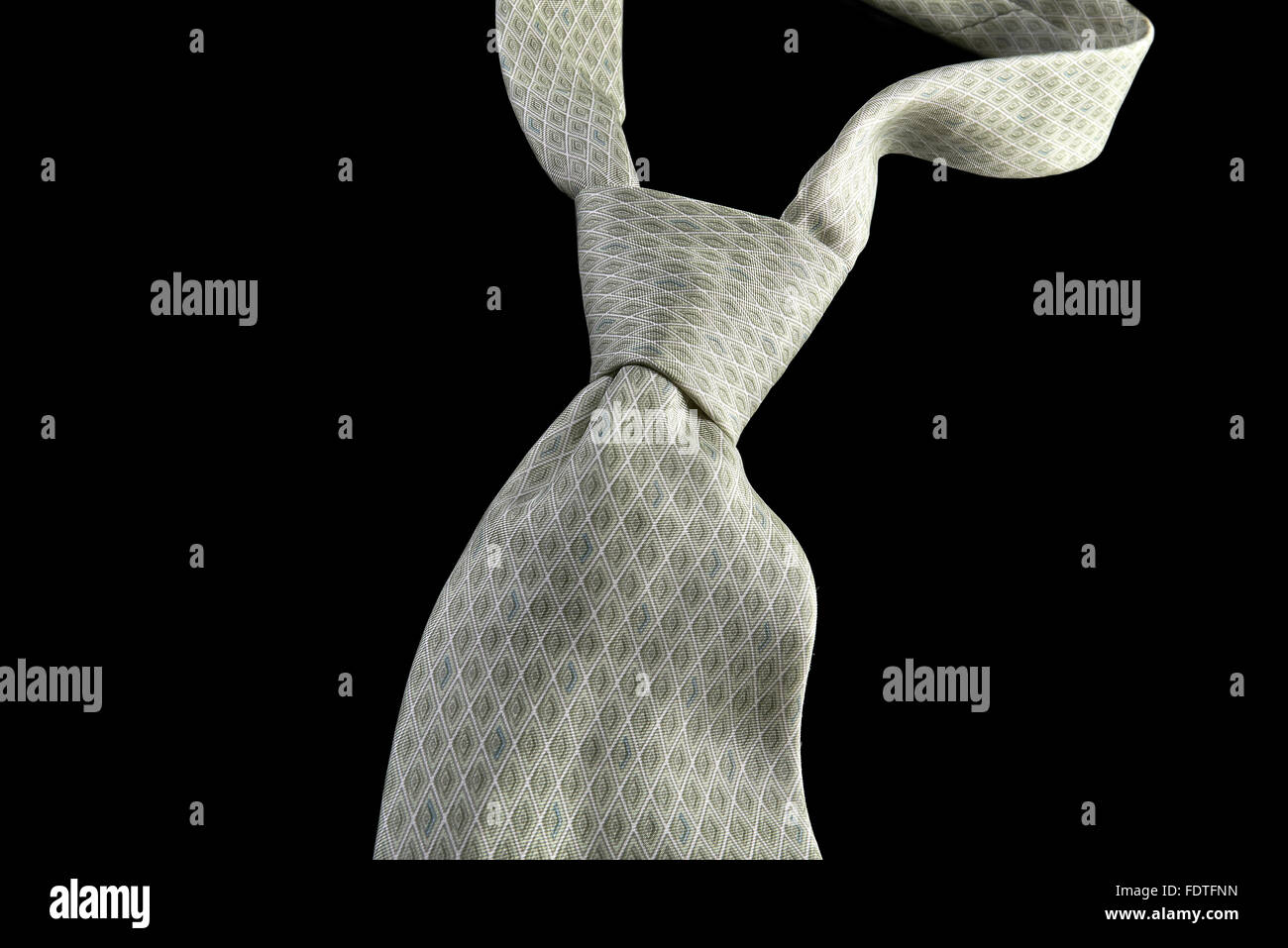 Soft green necktie, isolated on black background. - Stock Image