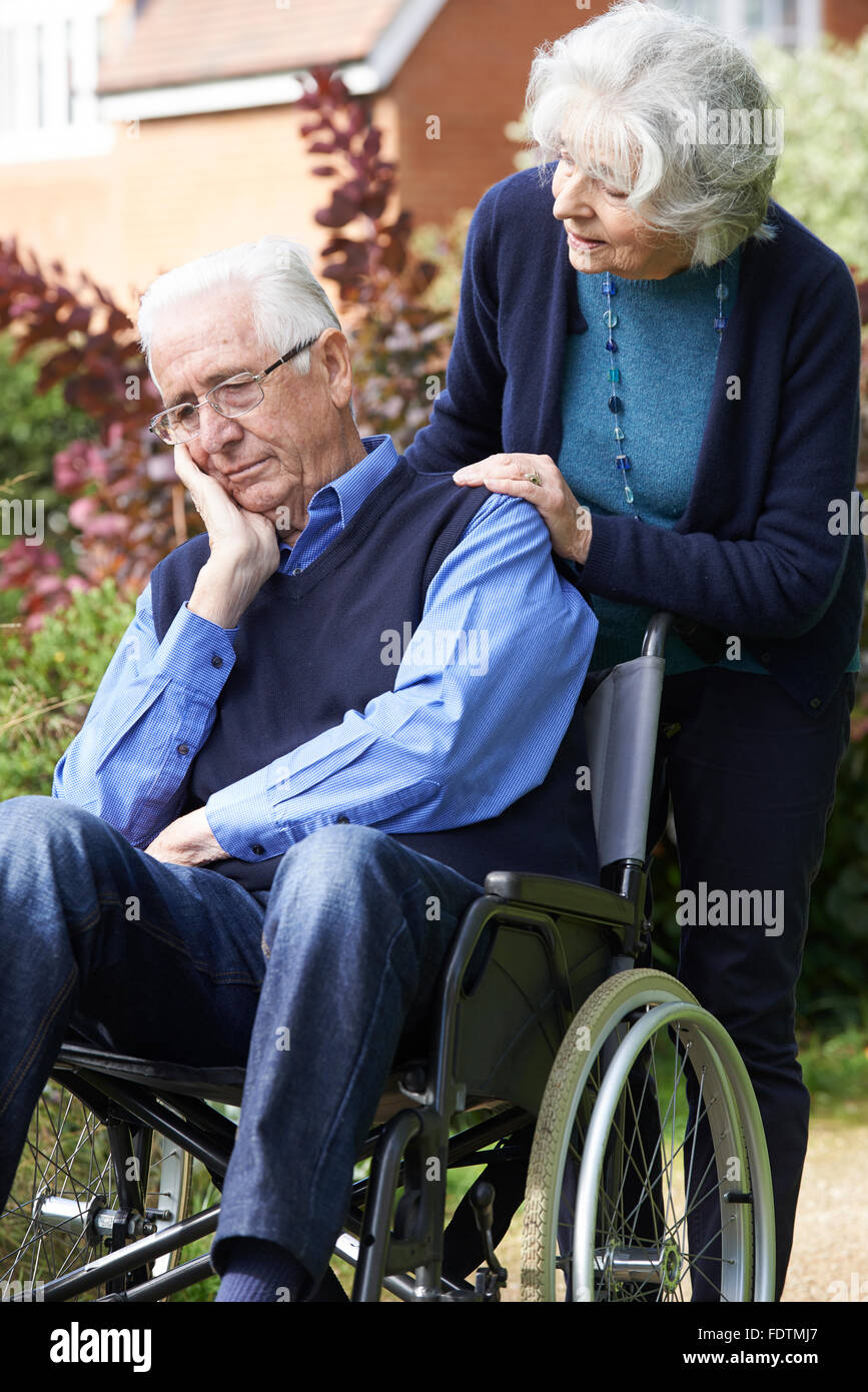Depressed Senior Man In Wheelchair Being Pushed By Wife - Stock Image
