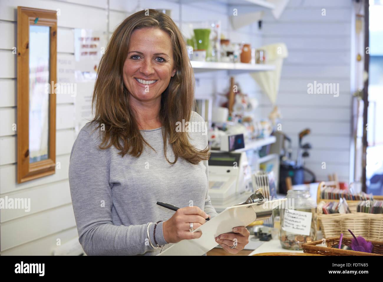 Portrait Of Volunteer Working In Charity Shop - Stock Image